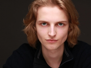 Young blonde blue eye man having a photo session in a studio in a black coat