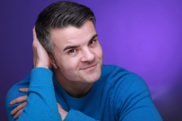 Keith Maynard posing to camera with blue jumper and purple background in the studio © Vincenzo Photography