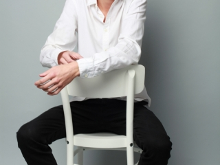 model sitting on a white hair in a whit shirt modelling in the studio