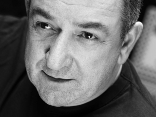 award winning actor ken stott portrait in black  and white in black top looking off camera