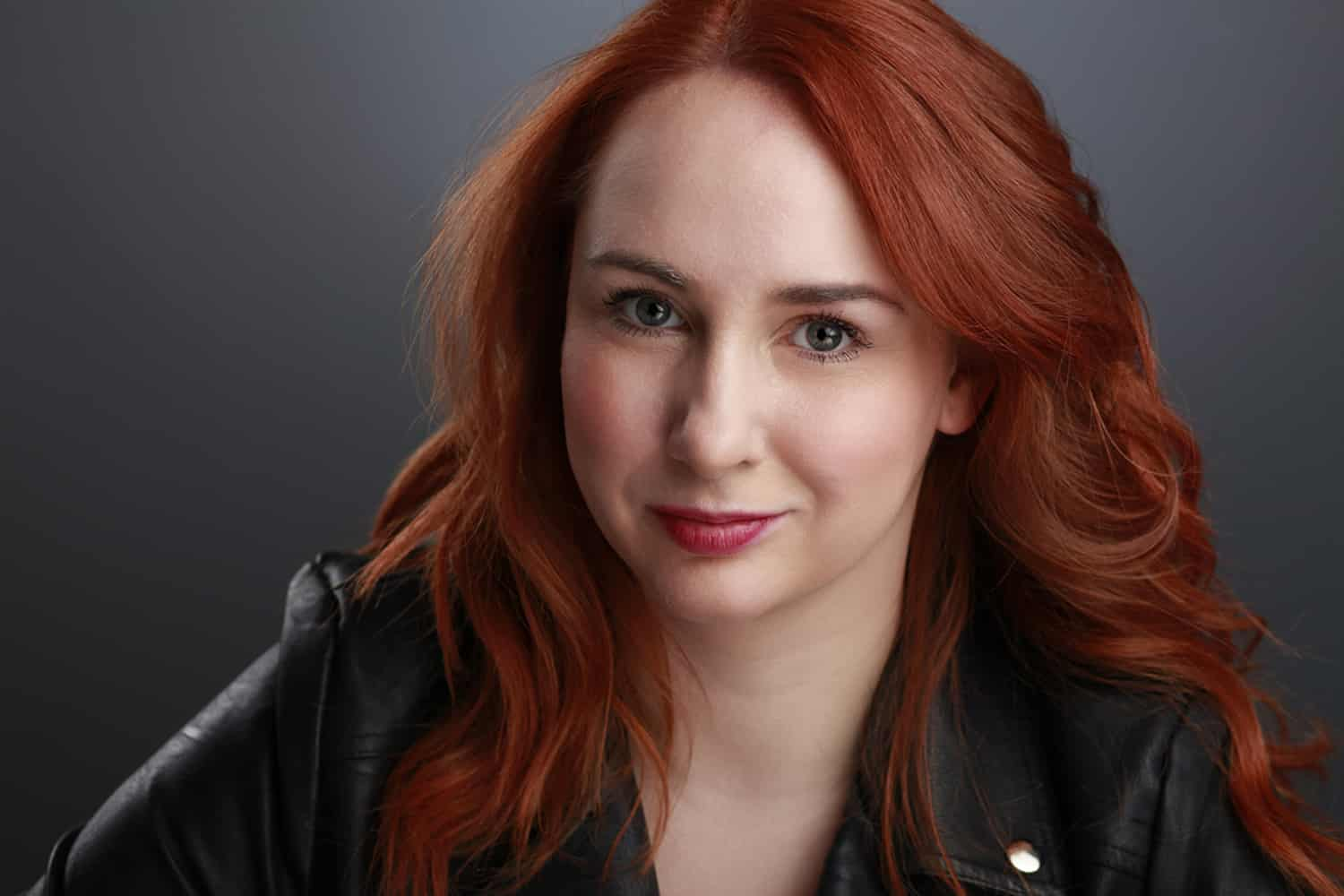 Red-Hair-Girl-Black -jacket-Photo-studio-grey-backdrop